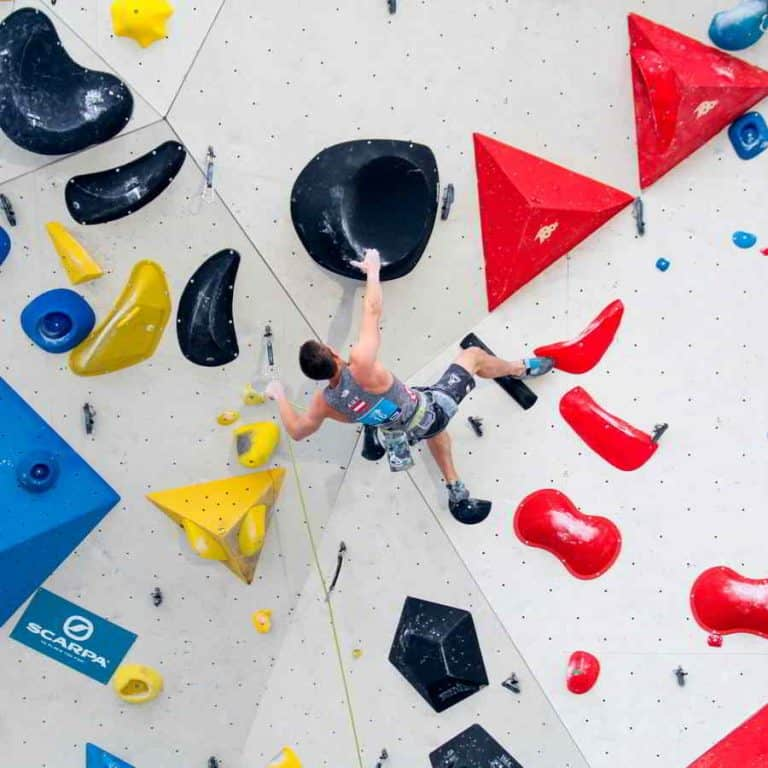 Climbing technique lead climbing male competitor on indoor wall